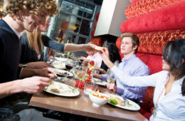Group of friends dining out in a trendy restaurant, having fun, drinking and eating