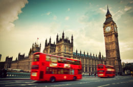 London, the UK. Red bus in motion and Big Ben, the Palace of Westminster. The icons of England in vintage, retro style